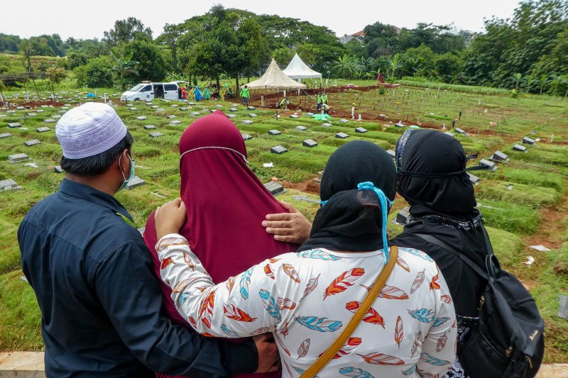 Family members of a victim of the coronavirus mourn during a funeral in Jakarta on March 31. BAY ISMOYO/AFP via Getty Images