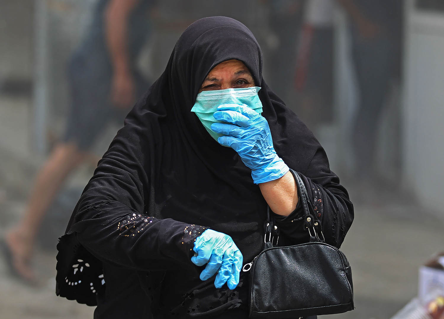 An Iraqi woman wearing protective gloves and mask walks by on a street in the Washash district, in western Baghdad, on April 6, during a disinfection campaign of the neighborhood to stem the spread of the novel coronavirus.