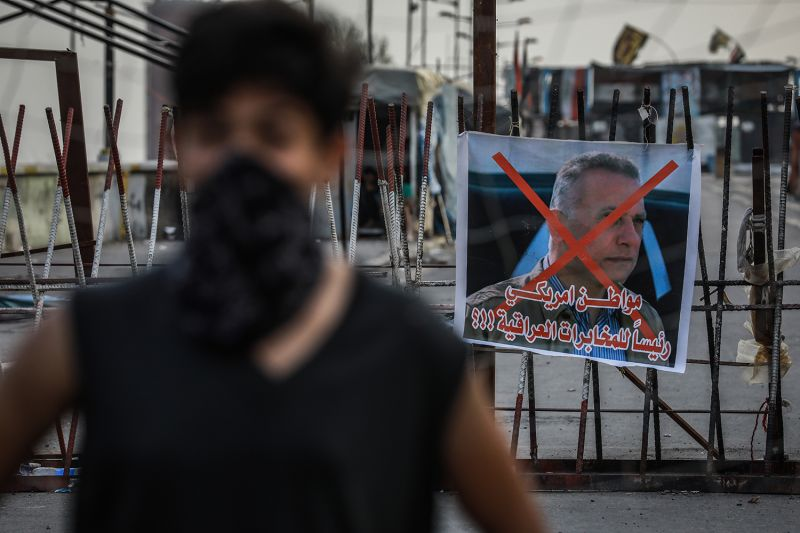A banner with a defaced picture of Mustafa al-Kadhimi, Iraq's former intelligence chief and new prime minister-designate, is seen behind an anti-government demonstrator in Baghdad's Tahrir Square on April 9.