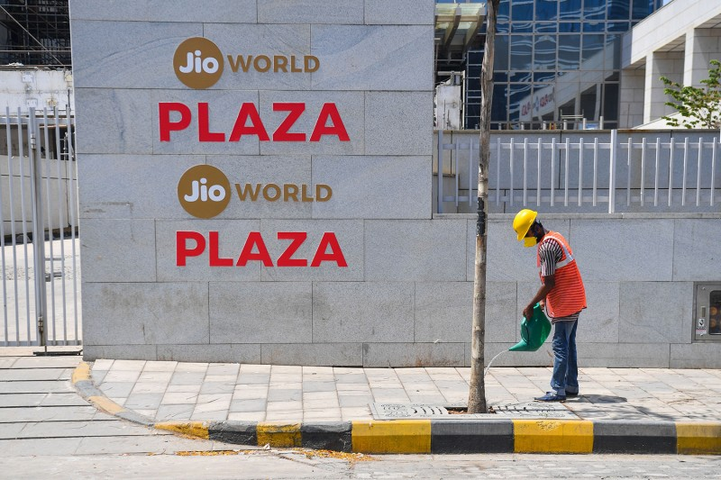 A man waters a tree outside the Jio World center in Navi Mumbai, India, on April 22.