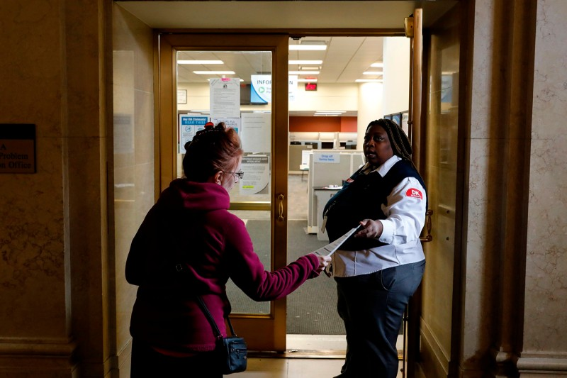 A security guard hands out an instruction sheet outside a State of Michigan Unemployment Agency office in Cadillac Place in Detroit on March 26. JEFF KOWALSKY/AFP via Getty Images