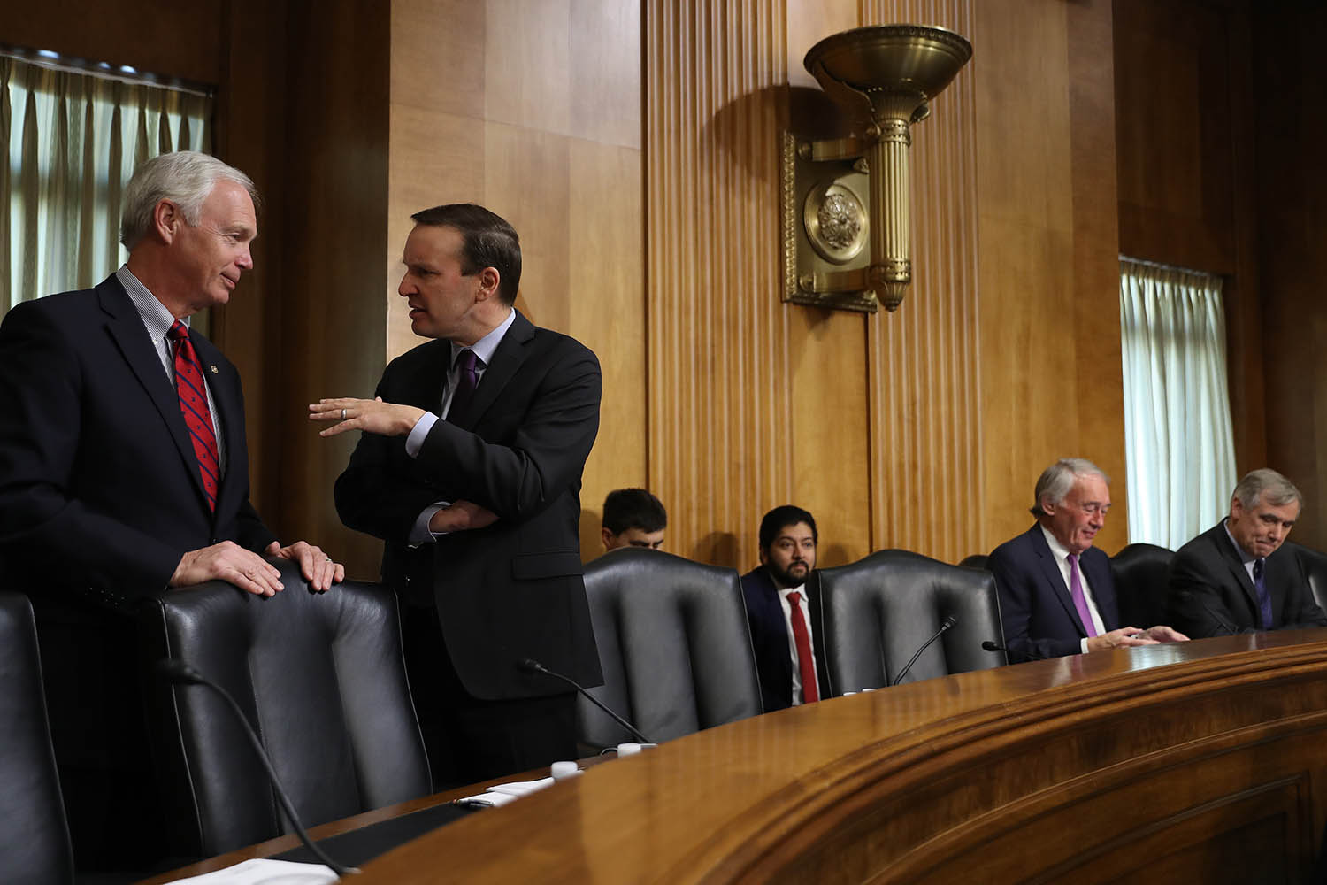 Senate Foreign Relations Committee members Sen. Ron Johnson, R-Wisconsin, (left) and Sen. Chris Murphy (D-Connecticutt) talk before a hearing in the Dirksen Senate Office Building on Capitol Hill in Washington on Dec. 3, 2019.