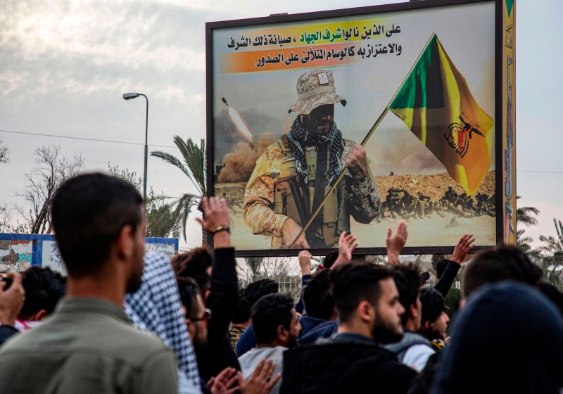 Protesters chant slogans as they walk past a pro-Kataib Hezbollah billboard during an anti-government demonstration.