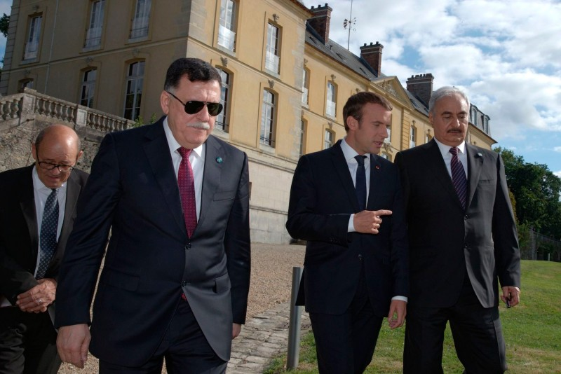 French President Emmanuel Macron walks with Libyan Prime Minister Fayez al-Sarraj and General Khalifa Haftar, commander of the Libyan National Army, after talks aimed at easing tensions in Libya.