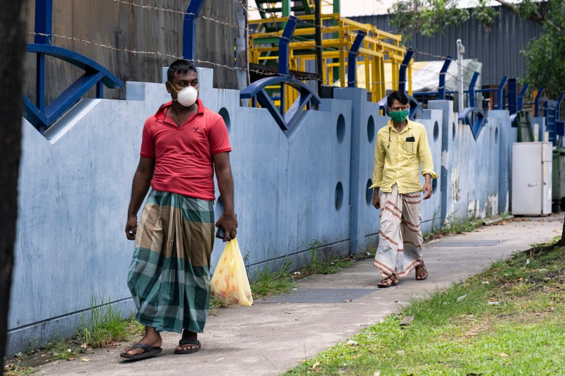 Migrant workers wearing protective face masks walk past a factory-converted dormitory.
