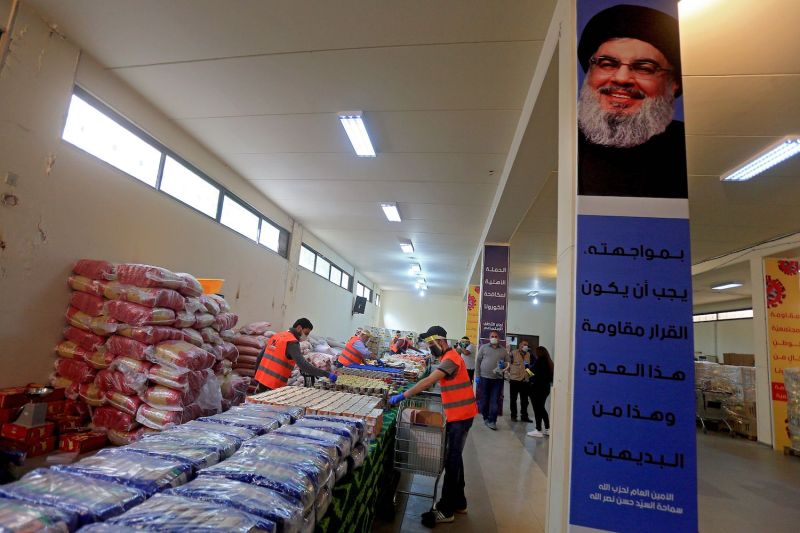 A picture taken during a guided tour organized by the Lebanese Shiite movement Hezbollah shows volunteers sorting food aid that will be distributed during the coronavirus pandemic in Beirut's southern suburbs on March 31. A poster on the wall shows the current leader of the movement, Hassan Nasrallah.
