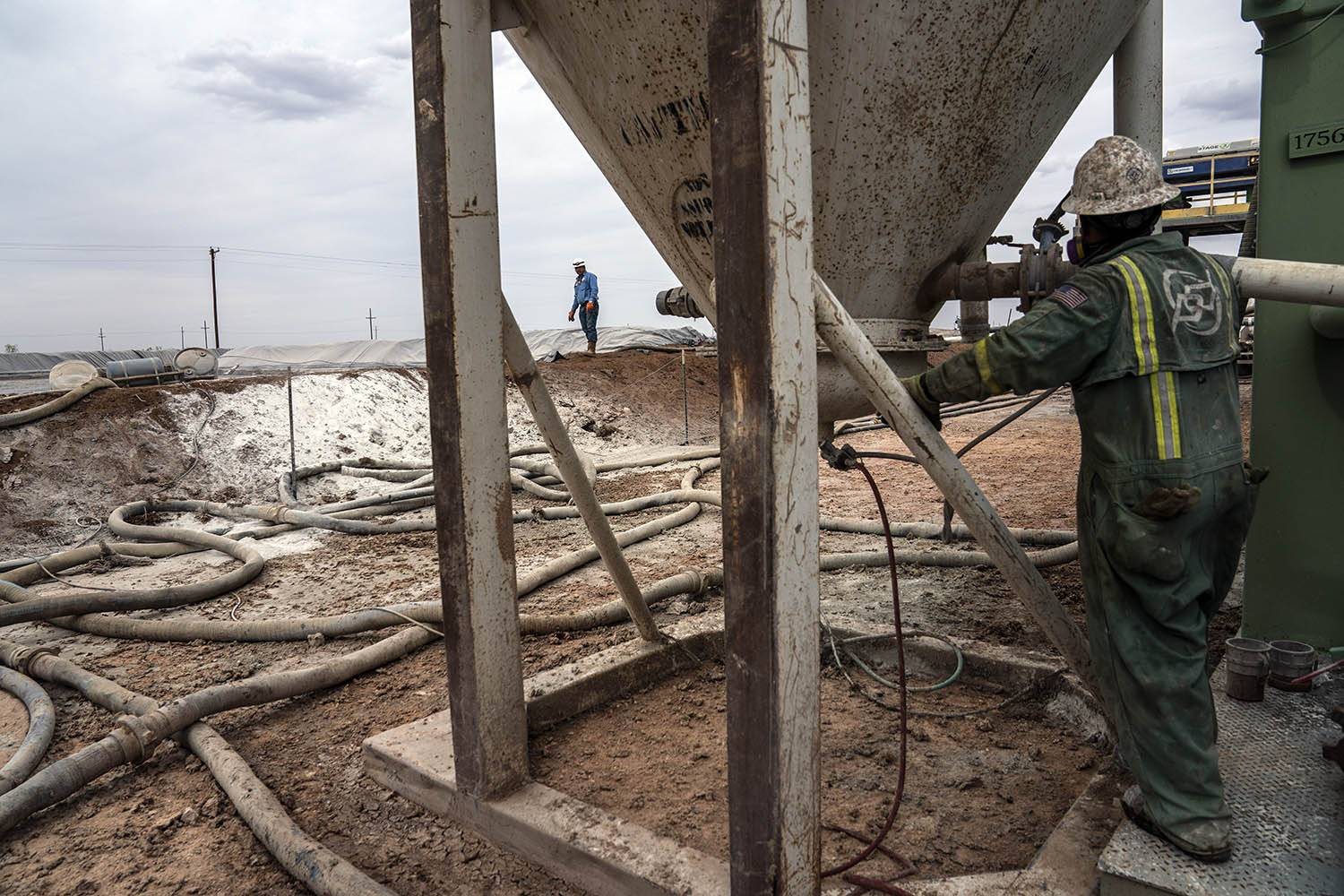 Workers extract oil from oil wells in the Permian Basin in Midland, Texas on May 1, 2018.