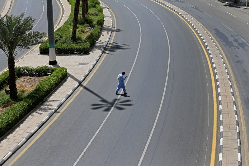 A man checks his phone as he crosses an empty street in Saudi Arabia's holy city of Mecca on April 3.