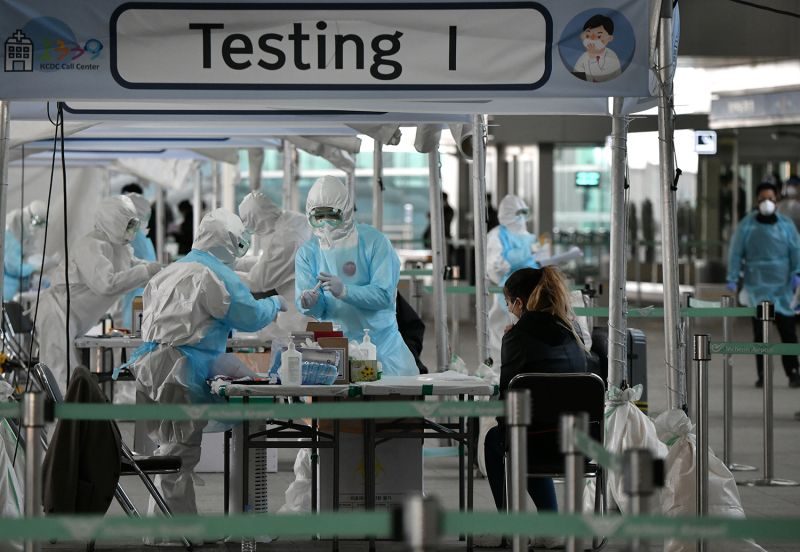 Medical staff take COVID-19 test samples from a foreign passenger at a virus testing booth outside Incheon International Airport, near Seoul, on April 1.