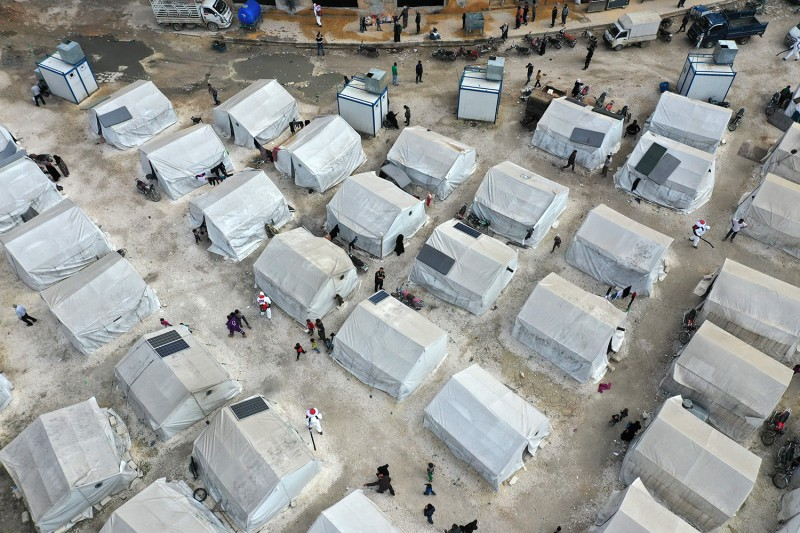 Sanitation workers disinfect a camp for displaced Syrians next to the Idlib municipal stadium on April 9.