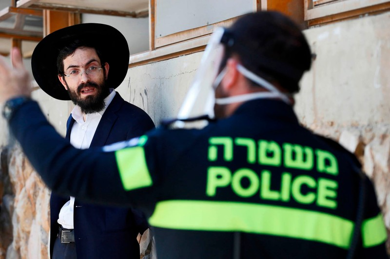 An Israeli police officer speaks to an ultra-Orthodox Jewish student at a Yeshiva in Bnei Barak, a city east of Tel Aviv with a large ultra-Orthodox Jewish population, on April 2.