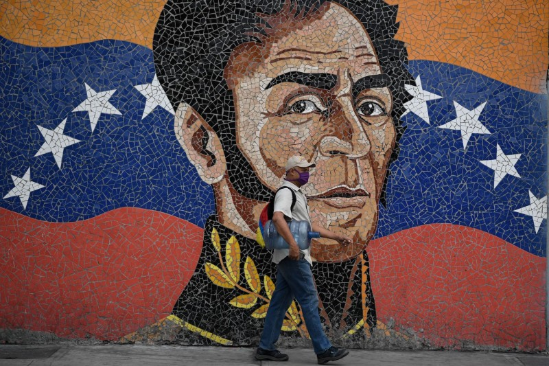 A man wearing a face mask walks past a mural depicting South American independence hero Simón Bolívar in Caracas on April 17, amid the coronavirus  outbreak.