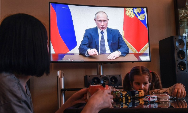 A woman watches a live broadcast of Russian President Vladimir Putin's address to the nation over the coronavirus outbreak.