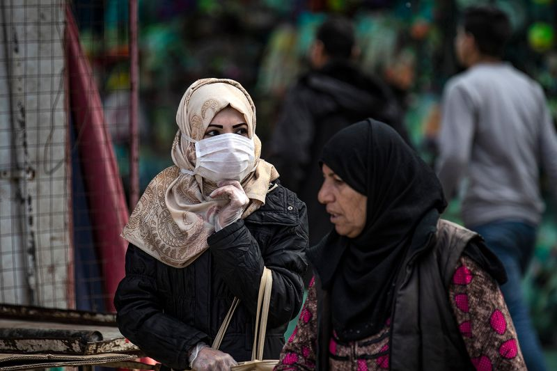 A woman wearing a protective mask walks along a street in northeast Syria.