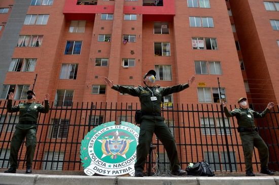 Police officers dance and encourage people to follow from their balconies and windows during a visit to a neighborhood in Bogota, Colombia, on April 8.