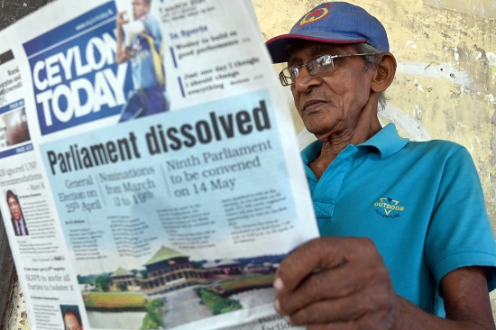 A man reads a newspaper with a headline on Sri Lanka's dissolution of parliament in Colombo on March 3.