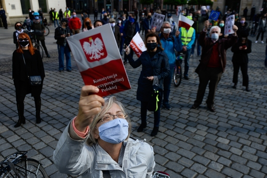 A woman waves a copy of Poland's Constitution as she takes part in an anti-government social distance protest in Warsaw during the country's Constitution Day anniversary May 3.