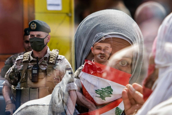 In this double-exposure photo, members of the Lebanese Armed Forces stand guard as citizens demonstrate against dwindling economic conditions at al-Nour Square in Tripoli on May 3.