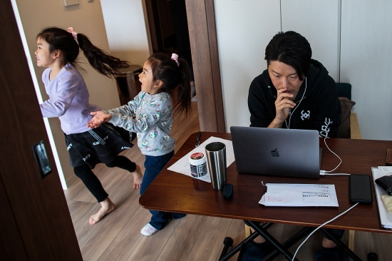 Yuki Sato, an employee at a start-up company, works from home in Tokyo on March 23 as his daughters Yurina (left) and Hinano play.