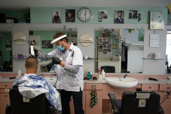 A stylist cuts hair in Switzerland.