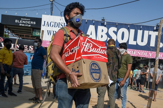 A man carries cases of beer from a liquor shop after the government eased a nationwide lockdown on alcohol in Gurgaon, India, on May 6.