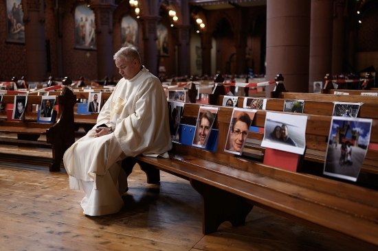 Abbot Vincent Marville prays in the Basilica of Neuchatel in Switzerland on May 3, surrounded by portraits of 400 parishioners unable to attend the Mass because of the pandemic.