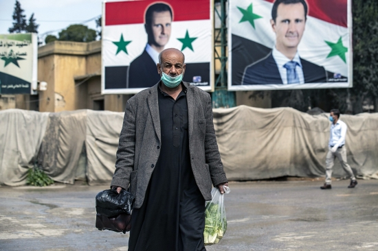 A Syrian man carries groceries as he walks past billboards of President Bashar al-Assad in the Kurdish-majority city of Qamishli on March 24.