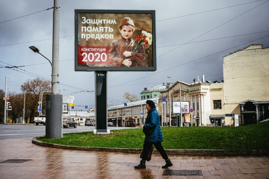 "A woman walks past a constitutional referendum billboard reading ""Let's protect the memory of our ancestors"" in Moscow on April 17. A constitutional referendum that would enable President Vladimir Putin to extend his time in office was set to be held April 22 but was postponed in light of the coronavirus."