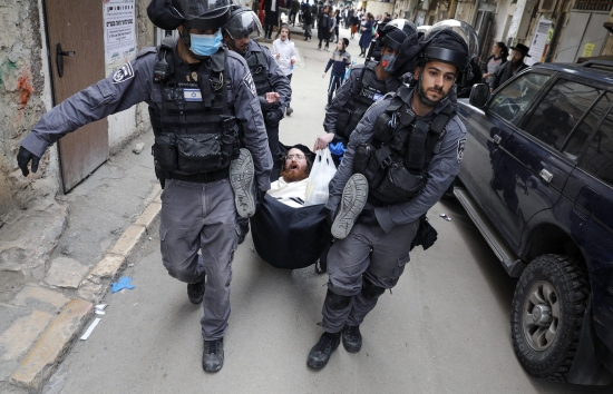 Israeli security forces arrest an ultra-Orthodox Jewish man as they close a synagogue in the Mea Shearim neighborhood of Jerusalem on March 30 amid efforts to curb the spread of the coronavirus.