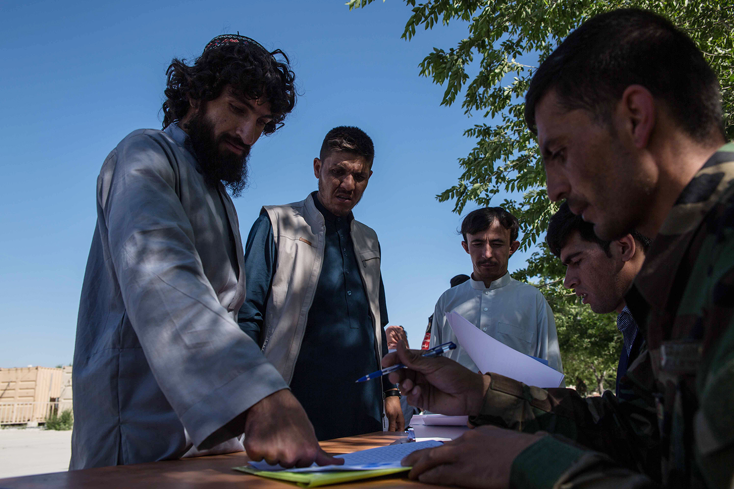 Prisoners sign or fingerprint a declaration saying that they won't return to the battlefield as they are freed from prison near Kabul on May 26. Each receives 5,000 Afghani ( USD) for food and their journey home.