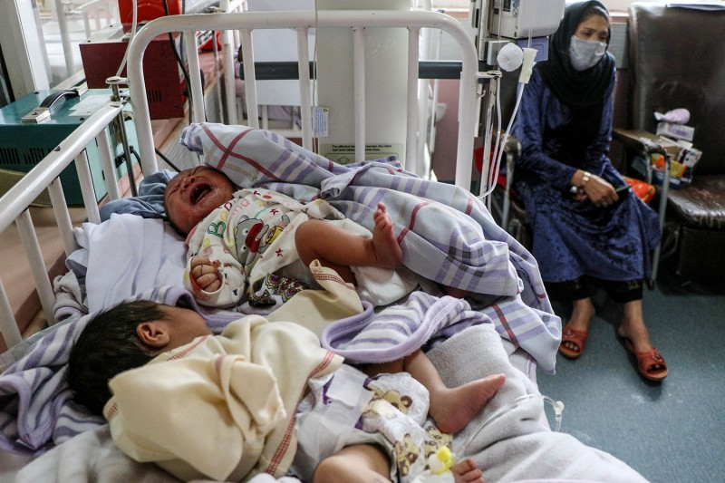 A woman sits next to newborn babies who lost their mothers following an attack in a maternity hospital in Kabul on May 13.