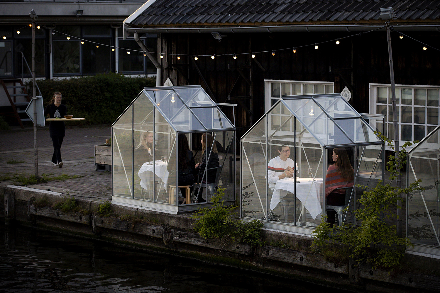 """People have dinner in a so-called """"quarantine greenhouses"""" at an Amsterdam restaurant May 5. ROBIN VAN LONKHUIJSEN/ANP/AFP via Getty Images"""