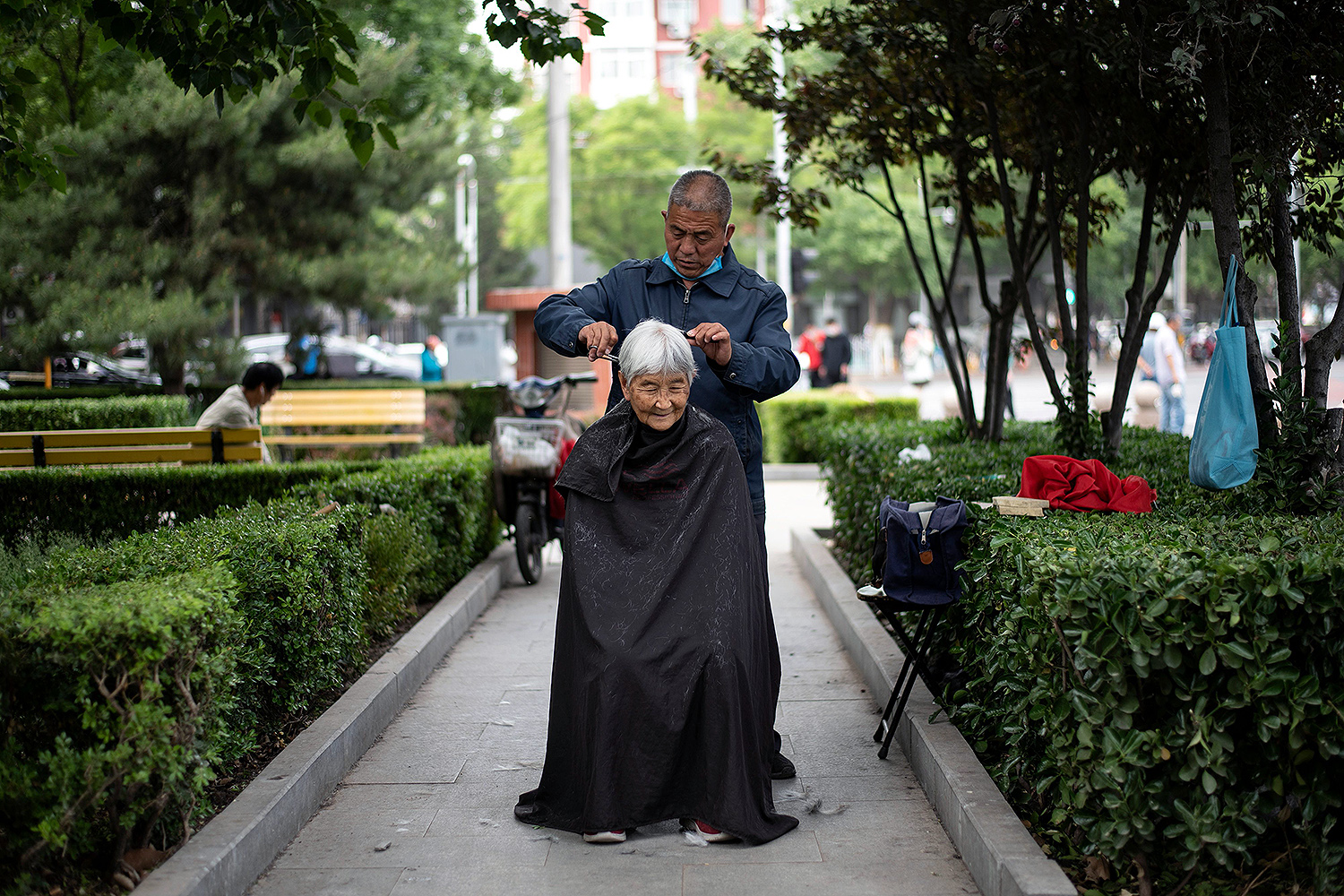 A barber cuts a woman's hair in a public park in Beijing on May 13. NOEL CELIS/AFP via Getty Images