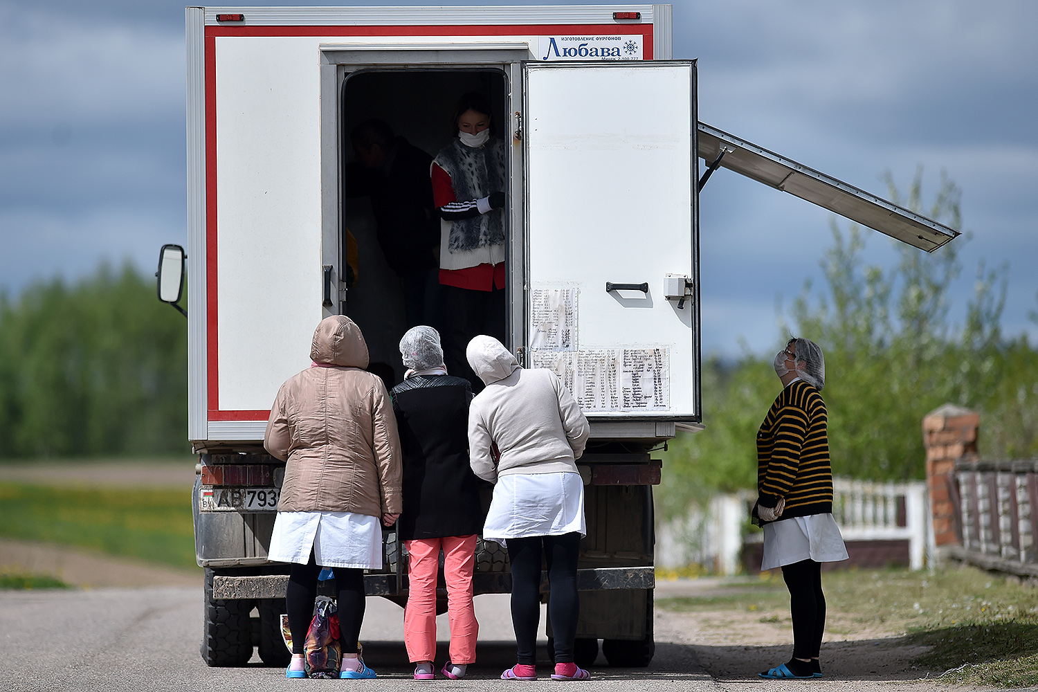 Shelter employees buy food for their patients from a truck transformed into a mobile shop in the village of Kreva, Belarus, northwest of Minsk, on May 14. SERGEI GAPON/AFP via Getty Images