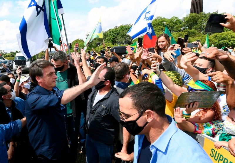 Brazil's President Jair Bolsonaro greets supporters upon arrival at Planalto Palace in Brasilia, on May 24, 2020, amid the COVID-19 coronavirus pandemic.