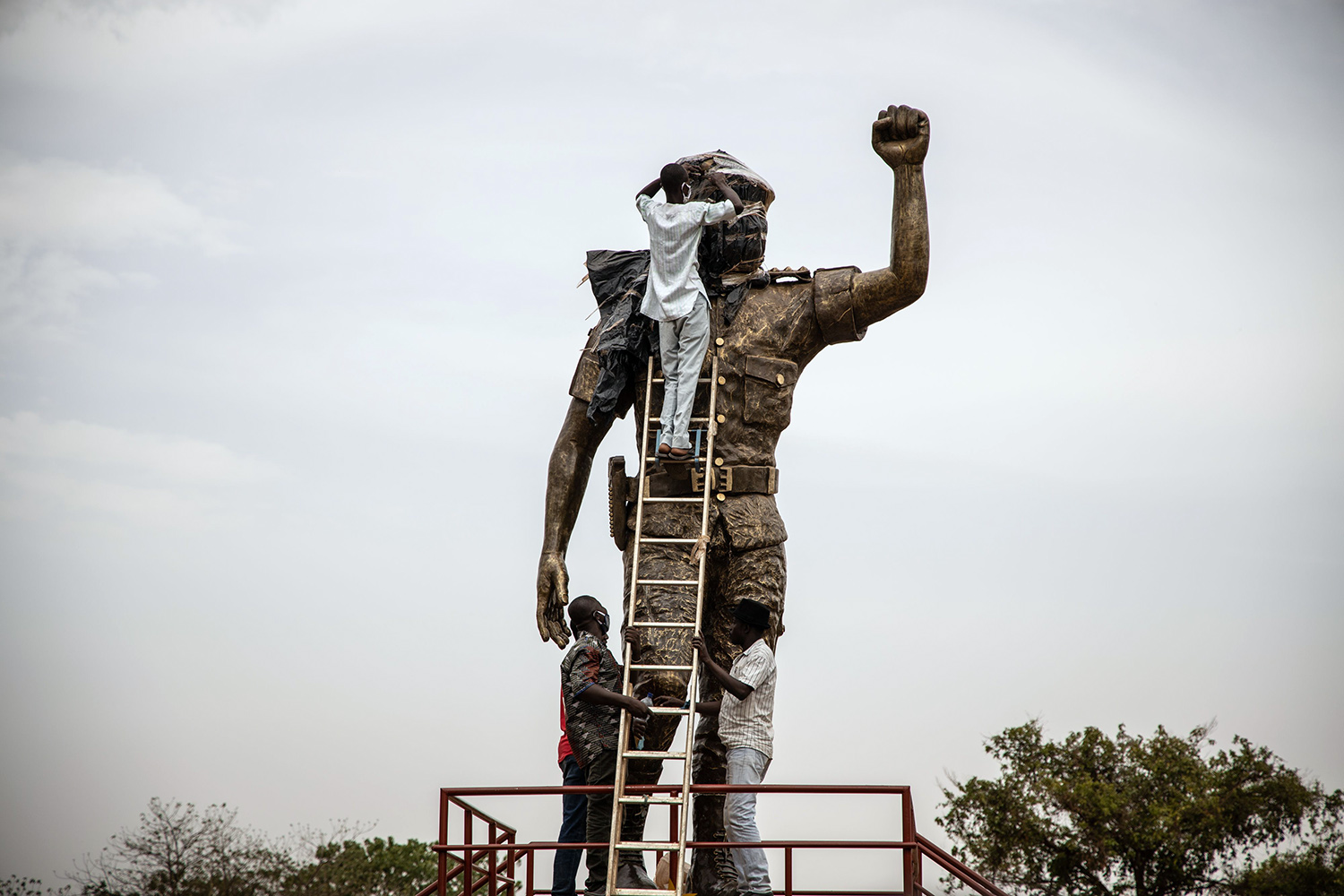 Employees unveil the second bronze statue of former Burkina Faso President Thomas Sankara, who was killed in 1987, at his memorial in Ouagadougou on May 17. The first version was removed because of complaints that it didn't bear a resemblance to the national hero. OLYMPIA DE MAISMONT/AFP via Getty Images