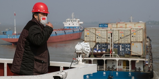 A worker watches over container ships at the port on the Yangtze River on April 12 as activities gradually resume after Wuhan, China, reopened following a lockdown for the coronavirus. China's central place in many global supply chains came back to haunt the global economy when the world's workshop shut down.
