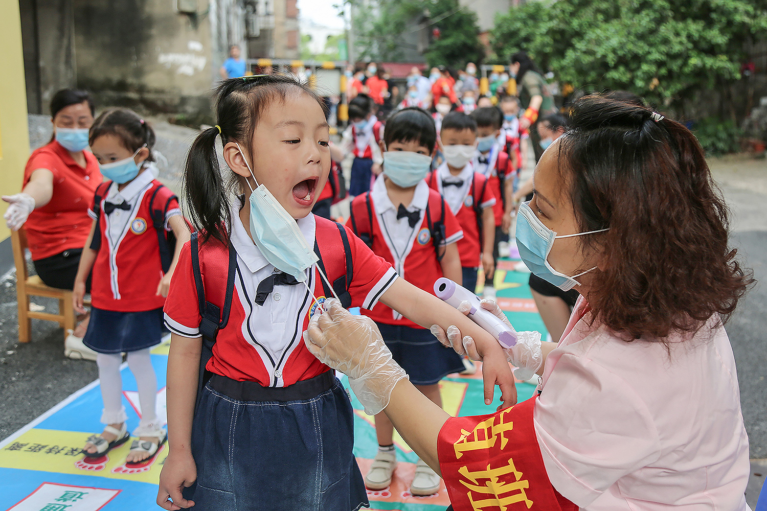 A staff member checks the oral health of a child before she enters a kindergarten classroom in Yongzhou, China, on May 11. STR/AFP via Getty Images