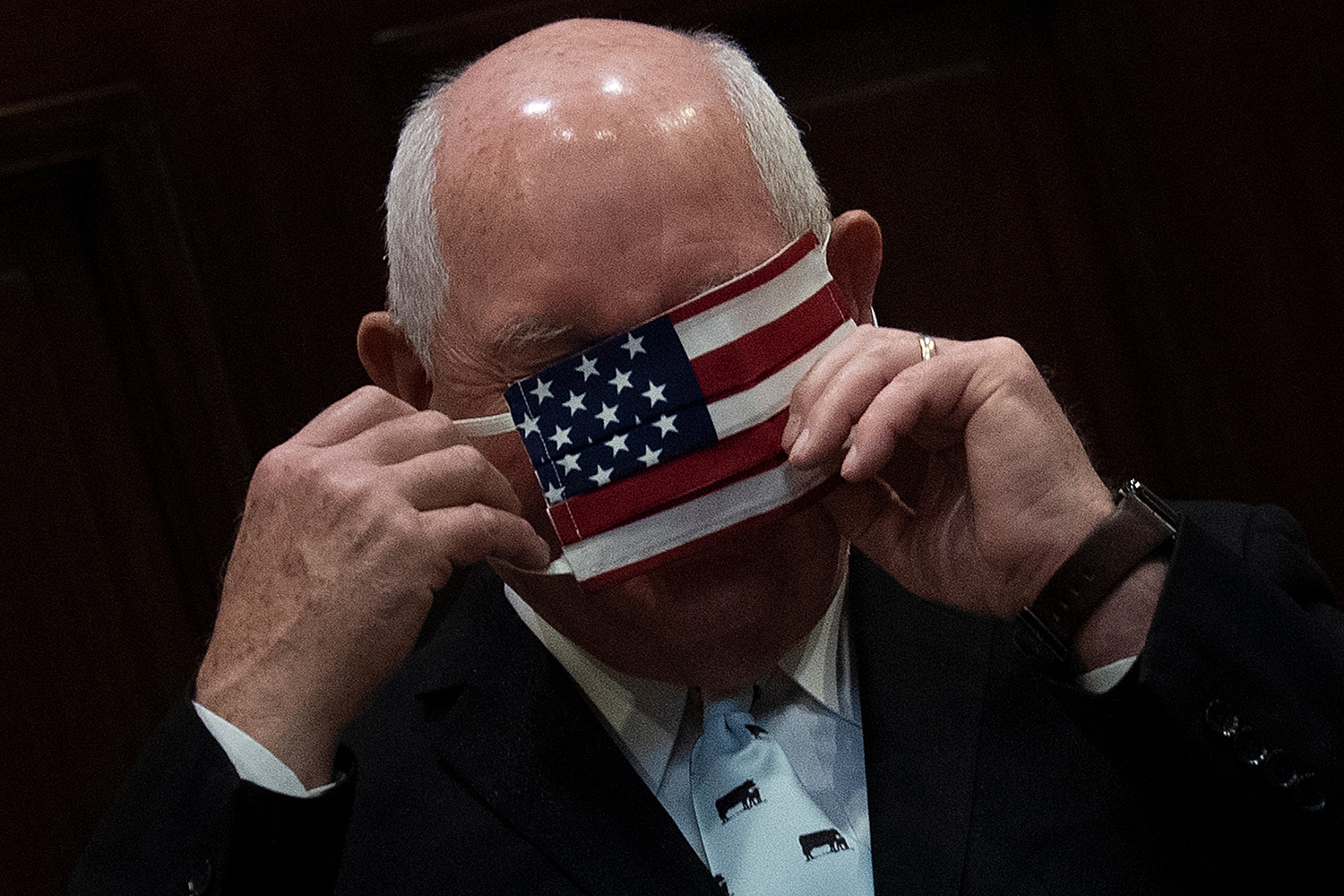 U.S. Secretary of Agriculture Sonny Perdue puts on a face mask in a meeting with the president about the country's food supply in the Roosevelt Room of the White House on May 19. BRENDAN SMIALOWSKI/AFP via Getty Images