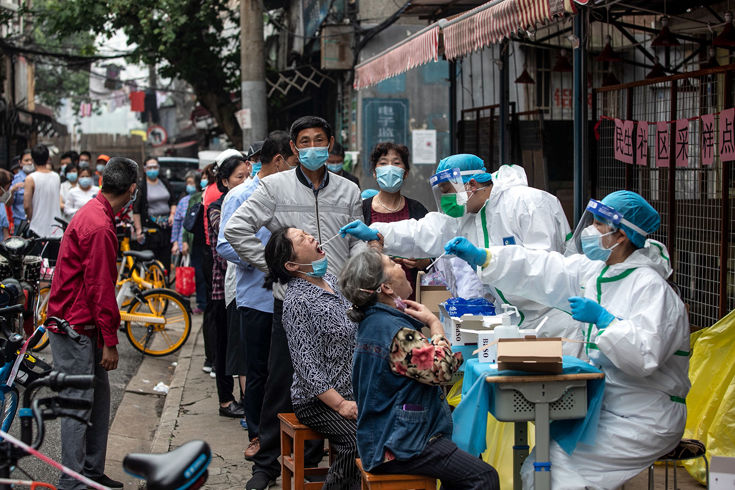 Medical workers test residents for COVID-19 on a street in Wuhan, China, on May 15. Wuhan authorities ordered mass testing for all 11 million residents after a new cluster of cases emerged. STR/AFP via Getty Images