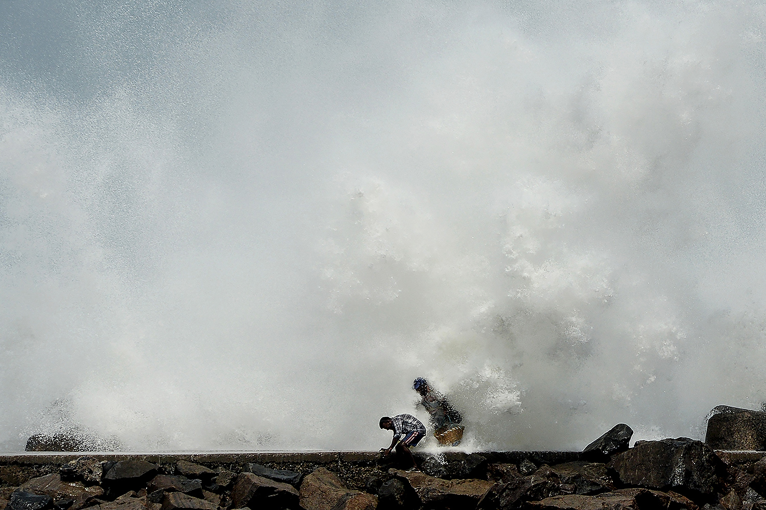 Men are hit by waves at Kasimedu fishing harbor in Chennai, India, on May 19 as Cyclone Amphan barrels toward the coast. ARUN SANKAR/AFP via Getty Images