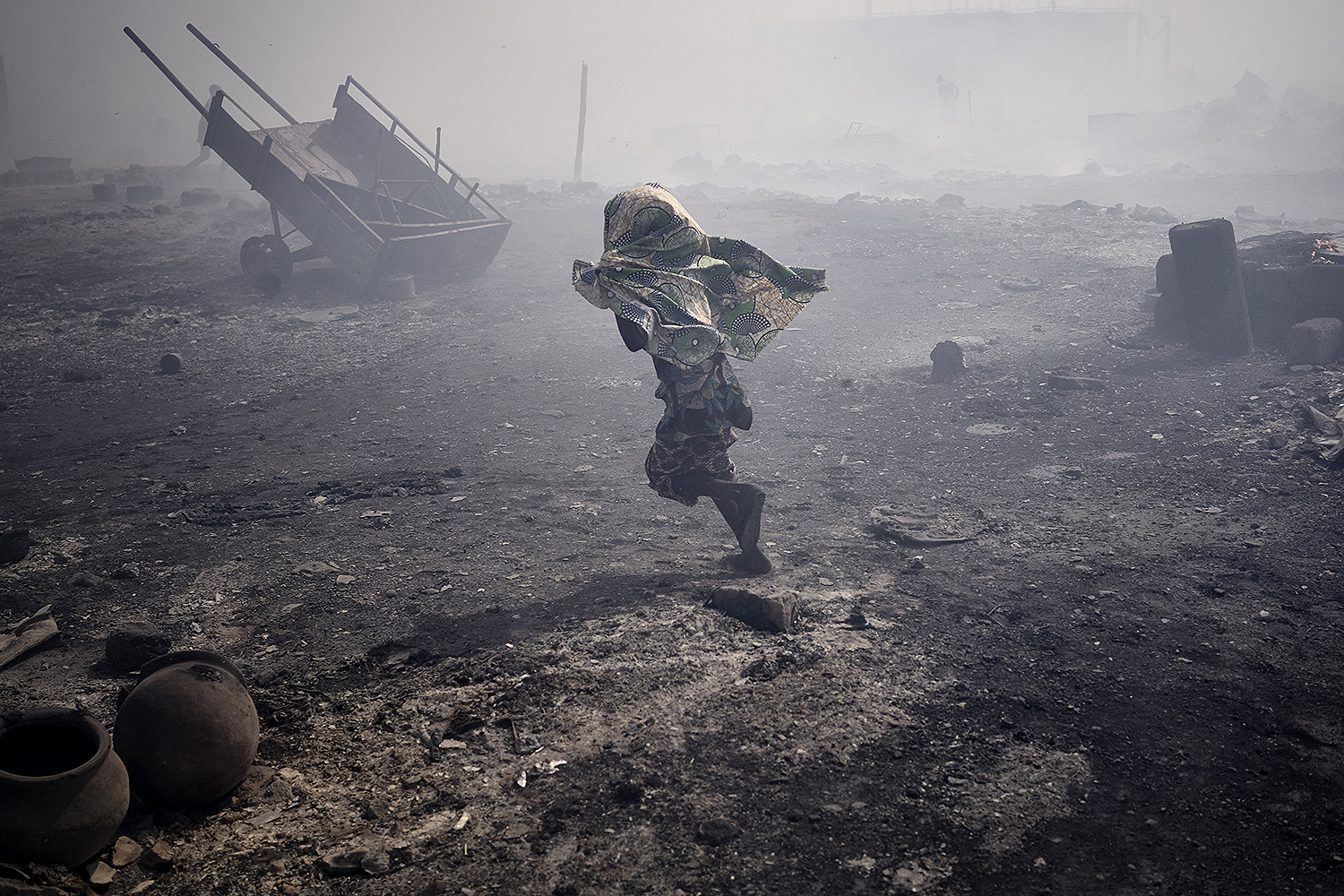 A girl runs between burnt huts in Faladie, an informal camp for displaced people, in Bamako, Mali, on April 28. A fire destroyed much of the camp, where more than 1,000 people who fled the violence in central Mali had found refuge. MICHELE CATTANI/AFP via Getty Images