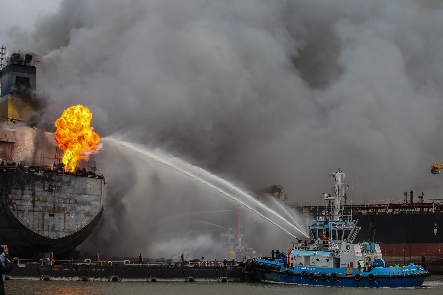 Firefighters onboard a vessel try to extinguish a fire on a tanker ship docked in Belawan, Indonesia, on May 11. IVAN DAMANIK/AFP via Getty Images