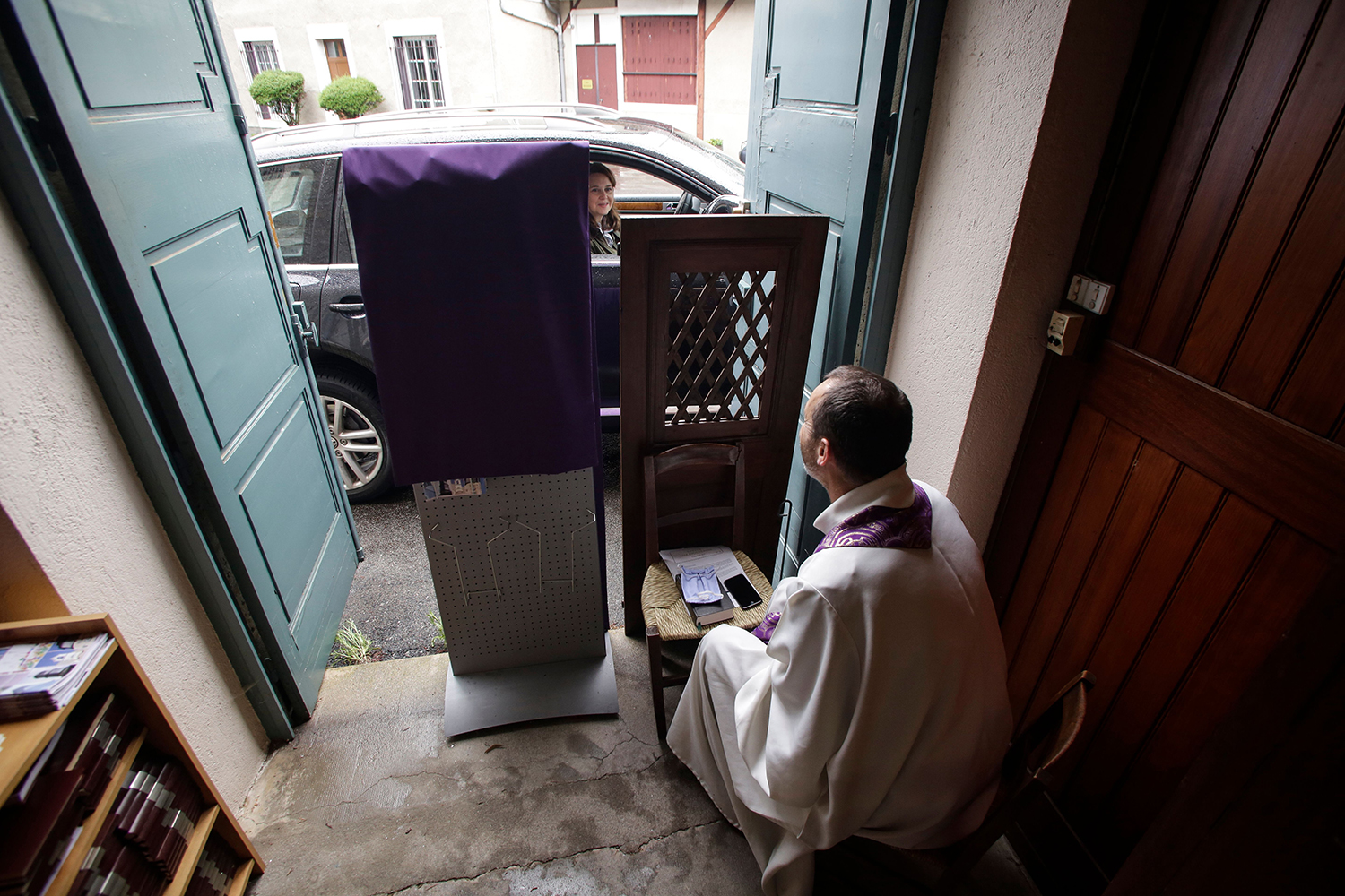 Catholic priest Vincent Poitau sits at an entrance to Sainte Jeanne d'Arc Church in Limoges, France, as a parishioner in a vehicle takes part in the sacrament of confession May 2. PASCAL LACHENAUD/AFP via Getty Images
