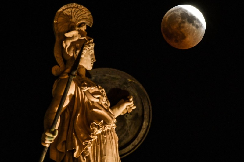 A statue of the ancient Greek goddess Athena is illuminated under a full moon in central Athens on July 27, 2018.