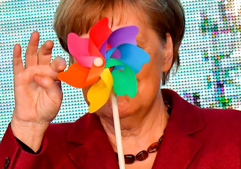 German Chancellor Angela Merkel poses with a toy wind wheel during the opening of the Arkona wind park in Sassnitz, northern Germany, on April 16, 2019.