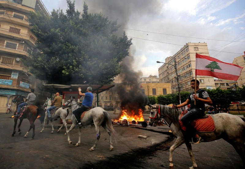 Lebanese protesters ride horses past burning tires in front of the house of former youth and sports minister Faisal Karami, during a protest against dire economic conditions in the coastal city of Tripoli on Oct. 18, 2019.