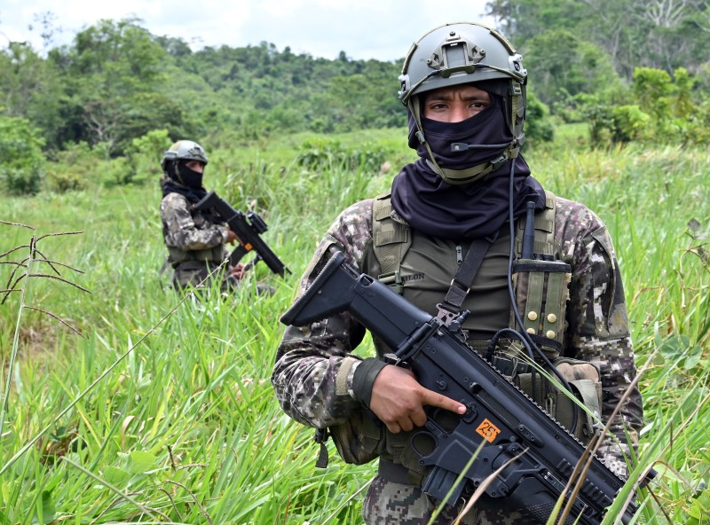 Peruvian Army soldiers stand guard during an operation to blow up a landing strip used by drug smugglers in the Amazon jungle, near Oxapampa, Peru, on Oct. 31, 2019.