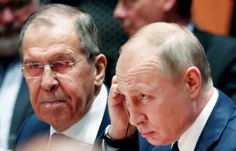 Russian President Vladimir Putin and Russia's Foreign Minister Sergei Lavrov at a peace summit on Libya