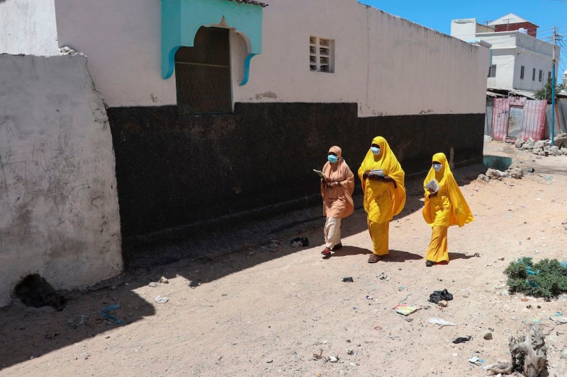 Students walk in a Mogadishu neighborhood wearing face masks as a protective measure against the coronavirus in Somalia on March 19.